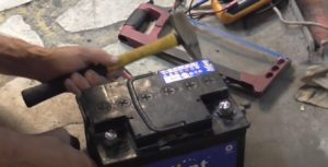 С помощью молотка обстукиваем крышку АКБ.